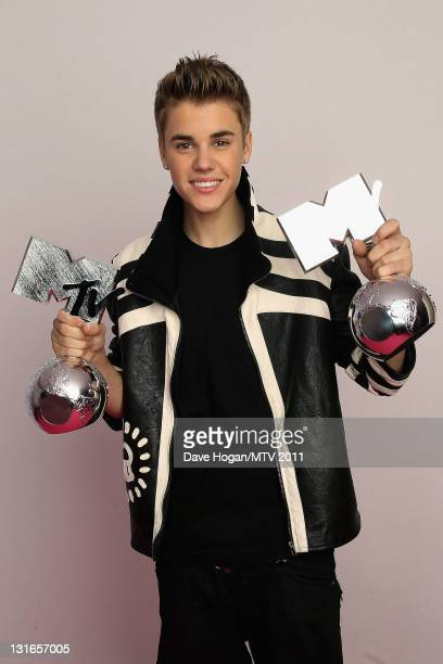 Singer Justin Bieber poses backstage with his awards for Best Male and Best Pop Act during the MTV Europe Music Awards 2011 at Odyssey Arena on...