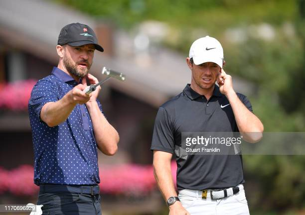 Singer Justin Timberlake of USA and Rory McIlroy of Northern Ireland discuss during the proam prior to the start of the Omega European Masters at...