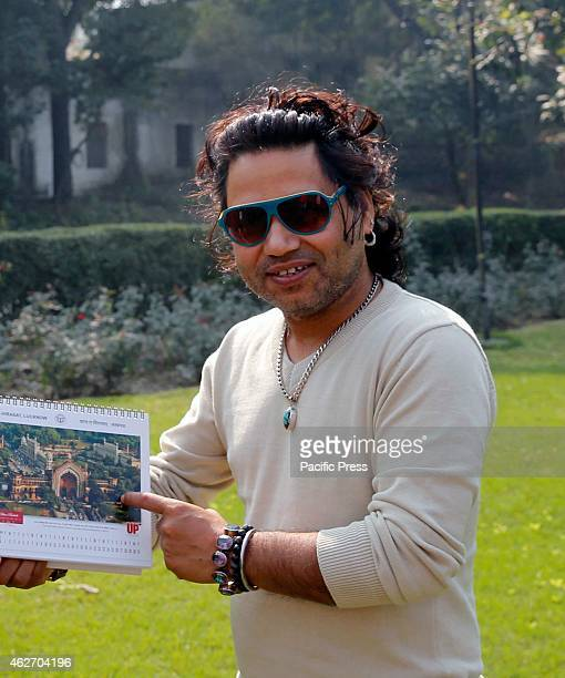 Singer Kailash Kher shows the calendar given to him during his visit at Lucknow