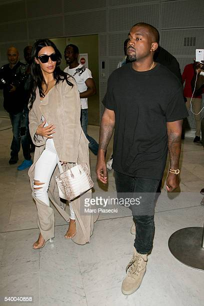 Singer Kanye West and wife Kim Kardashan West arrive at CharlesdeGaulle airport on June 14 2016 in Paris France