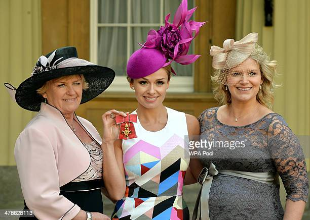 Singer Katherine Jenkins holds her OBE with mother Susan and sister Laura Johnson during an Investiture Ceremony at Buckingham Palace on March 14...