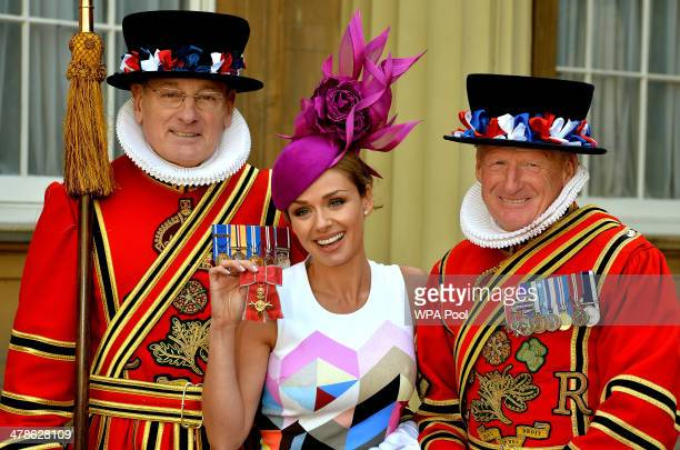 Singer Katherine Jenkins holds her OBE with two Yeoman Warders during an Investiture Ceremony at Buckingham Palace on March 14 2014 in London England