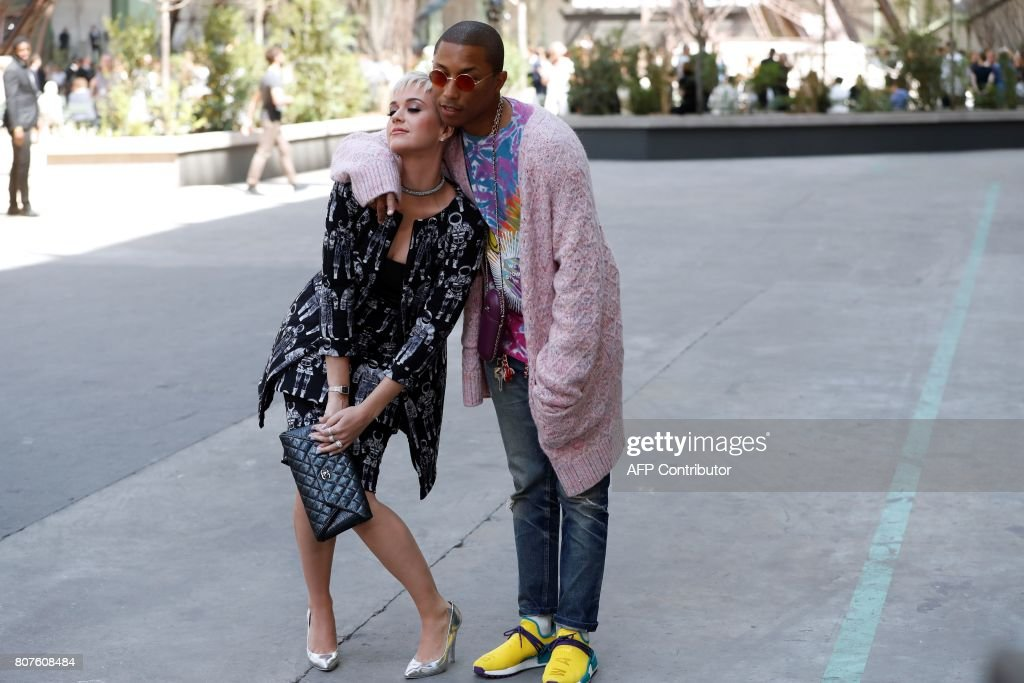 TOPSHOT - US singer Katy Perry (L) and US singer Pharrell Williams pose during the photocall before Chanel 2017-2018 fall/winter Haute Couture collection show in Paris on July 4, 2017. / AFP PHOTO / Patrick KOVARIK