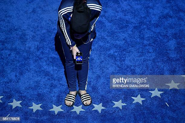 Singer Katy Perry looks down at her feet with her mobile phone during rehearsal before the final day of the 2016 Democratic National Convention at...
