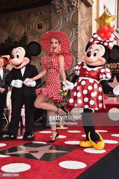 Singer Katy Perry stands next to Mickey Mouse and Minnie Mouse during a star ceremony in celebration of the 90th anniversary of Disney's Minnie Mouse...