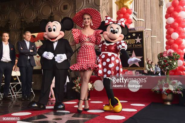 Singer Katy Perry stands on stage next to Mickey Mouse and Minnie Mouse during a star ceremony in celebration of the 90th anniversary of Disney's...