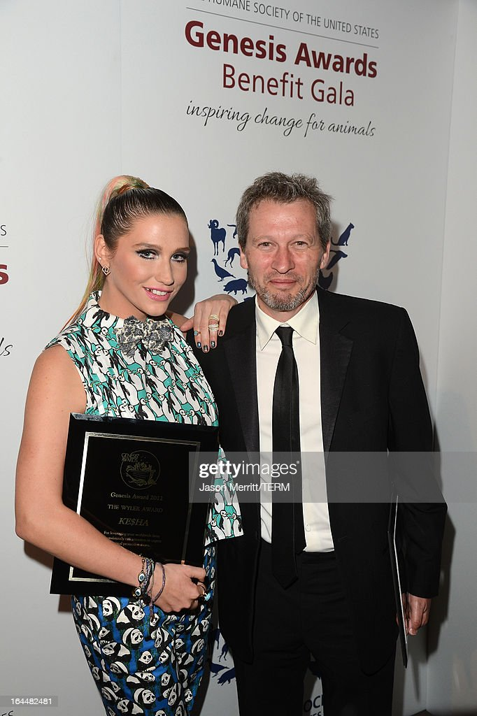 Singer Ke$ha poses backstage, after receiving The Wyler Award, with director Ken Kwapis at The Humane Society of the United States 2013 Genesis Awards Benefit Gala at The Beverly Hilton Hotel on March 23, 2013 in Los Angeles, California.