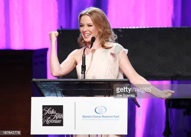 """Singer Kylie Minogue accepts the 2013 Courage Award onstage during EIF Women's Cancer Research Fund's 16th Annual """"An Unforgettable Evening""""..."""