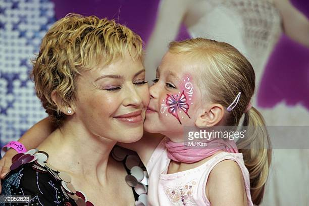 Singer Kylie Minogue is kissed by her fan Megan Hondius during a signing of her new book The Showgirl Princess at Waterstone's Oxford Street on...