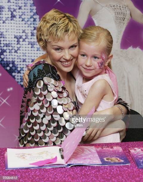 Singer Kylie Minogue poses with her fan Megan Hondius duringh a signing of her new book 'The Showgirl Princess' at Waterstone's Oxford Street on...