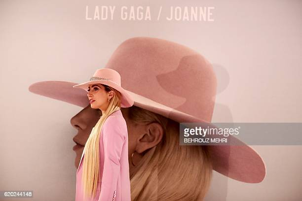 US singer Lady Gaga poses for photographers in front of her new album cover during a photo call to promote the album Joanne in Tokyo on November 2...