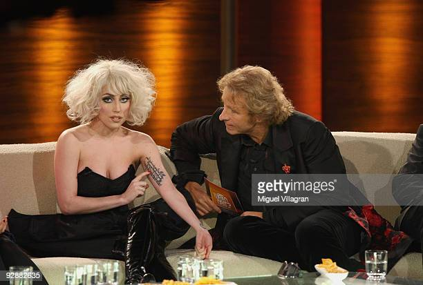 Singer Lady Gaga sits next to host Thomas Gottschalk during the 'Wetten dass...?' show at the Volkswagenhalle and shows off her tattoo of a Rilke...