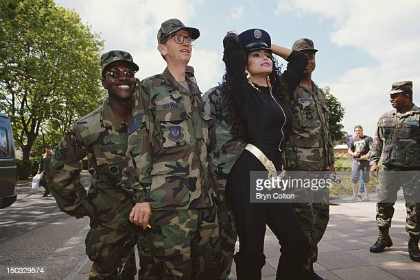 Singer LaToya Jackson poses with servicemen Bradley Holman and Thompson of the United States Air Forces in Europe at RAF Mildenhall in Sussex May...