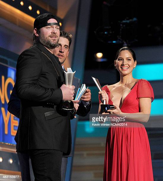 Singer Lee Brice accepts the Song of the Year award for 'I Drive Your Truck' onstage from NFL quarterback Aaron Rodgers and actress Olivia Munn...