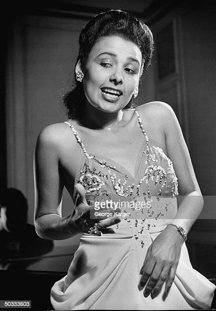Singer Lena Horne singing the lyrics People say in Boston even beans do it Cole Porter's Let's Do It w/o a microphone in front of rapt guests in...