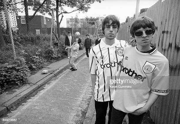 Singer Liam Gallagher and his guitarist brother Noel Gallagher of rock band Oasis pose in Manchester City football shirts 9th May 1994 Other band...