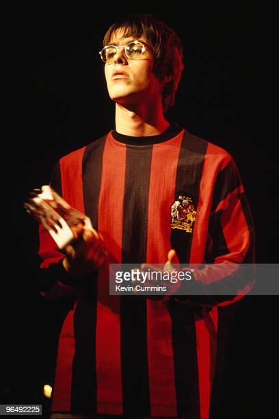 Singer Liam Gallagher performing on stage with rock group Oasis 1994 He is wearing a Manchester City football shirt