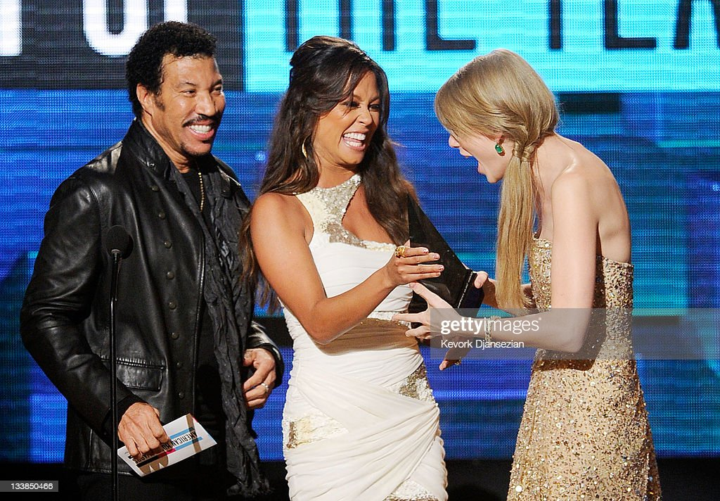 Singer Lionel Richie and TV personality Vanessa Lachey present singer Taylor Swift with Artist of the Year award onstage at the 2011 American Music Awards held at Nokia Theatre L.A. LIVE on November 20, 2011 in Los Angeles, California.