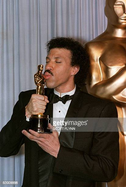 US singer Lionel Richie kisses his Oscar after he was awarded he golden statue at the 58th Annual Academy Awards 24 March 1986 in Hollywood Ca for...