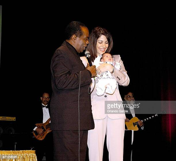 Singer Lou Rawls, his wife Nina Malek Inman and baby Aiden Allen Rawls appear on stage at the inaugural event of the Lou Rawls Center For The...