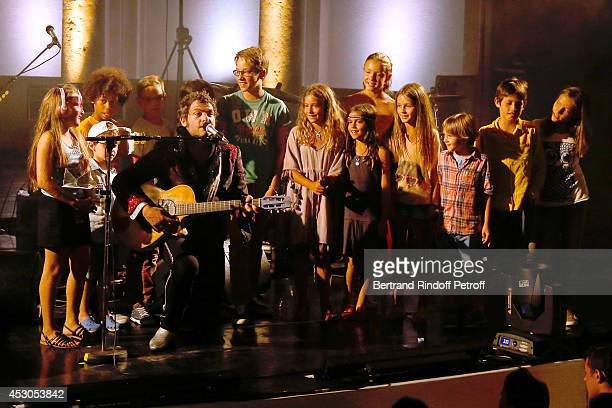 Singer 'M' alias Matthieu Chedid singing with children as he gives a concert during the 30th Ramatuelle Festival on August 1 2014 in Ramatuelle France