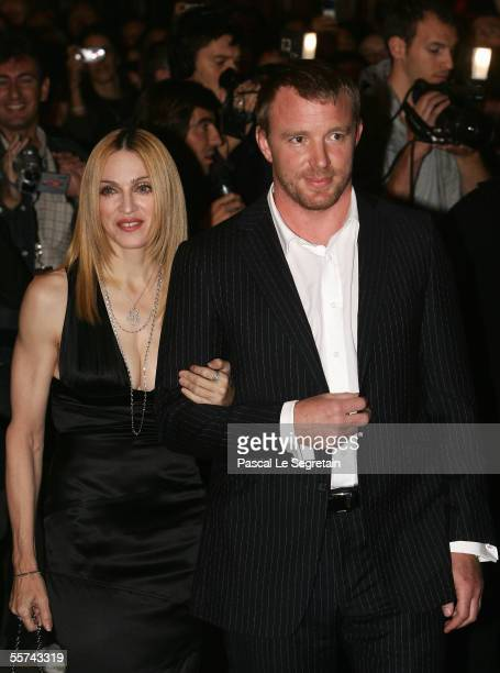 Singer Madonna and her husband British director Guy Ritchie arrive to attend the French premiere of Revolver at the Gaumont Marignan cinema on...