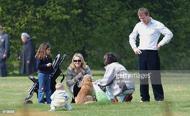 Singer Madonna greets a dog and its owner while Madonna's husband producer Guy Ritchie and her children Lourdes and Rocco watch during a walk in Hyde...