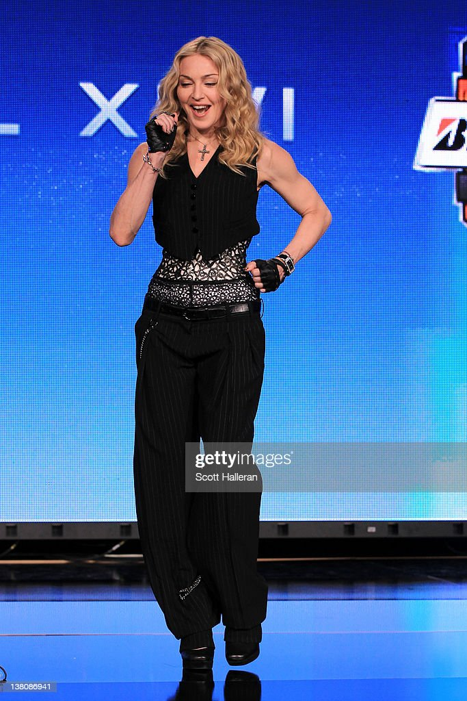 Singer Madonna performs a salsa dance after she was asked a question about Victor Cruz #80 of the New York Giants during a press conference for the Bridgestone Super Bowl XLVI halftime show at the Super Bowl XLVI Media Center in the J.W. Marriott Indianapolis on February 2, 2012 in Indianapolis, Indiana.