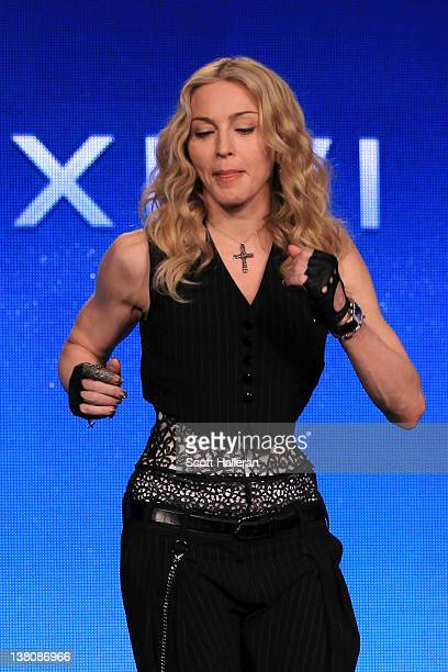 Singer Madonna performs a salsa dance after she was asked a question about Victor Cruz of the New York Giants during a press conference for the...