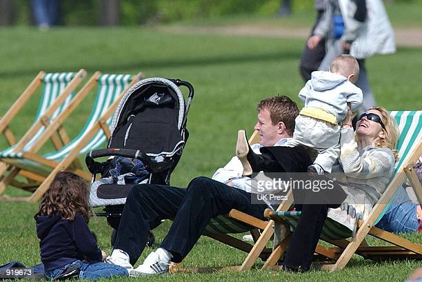 Singer Madonna plays with her son Rocco while her husband producer Guy Ritchie and daughter Lourdes relax during an outing in Hyde Park April 21 2002...