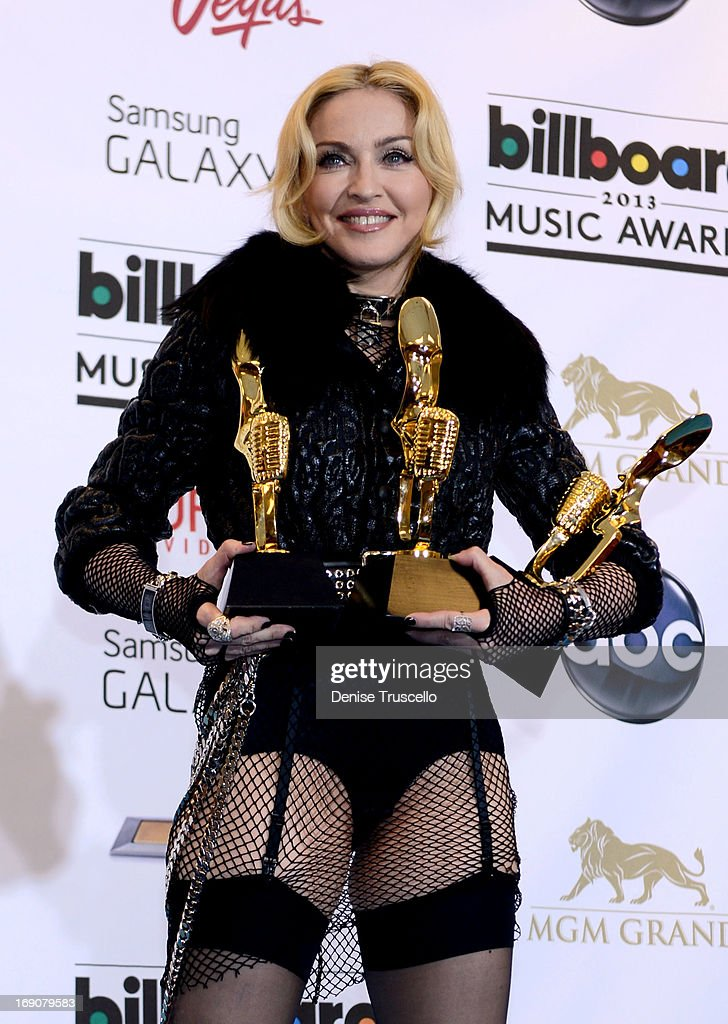 Singer Madonna poses with awards in the press room during the 2013 Billboard Music Awards at the MGM Grand Garden Arena on May 19, 2013 in Las Vegas, Nevada.