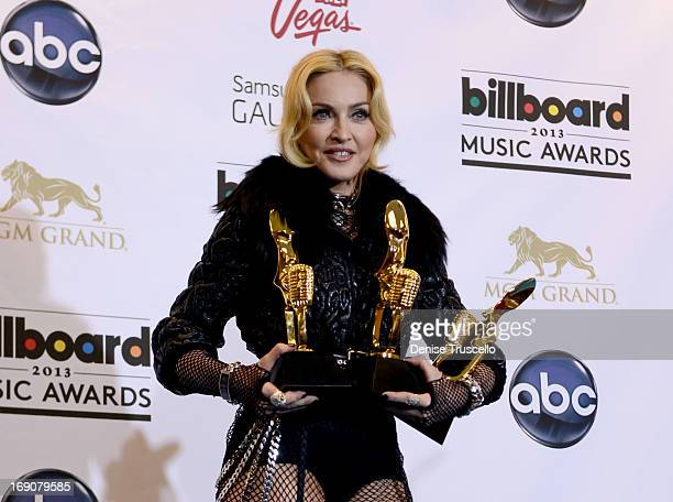 Singer Madonna poses with awards in the press room during the 2013 Billboard Music Awards at the MGM Grand Garden Arena on May 19, 2013 in Las Vegas,...
