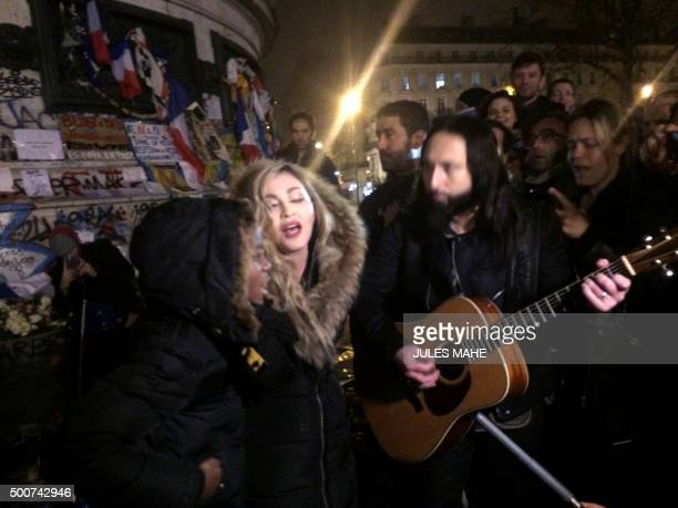 TOPSHOT US singer Madonna sings next to her guitarist Monte Pittman and her son David Banda on December 10 2015 at the place de la Republique in...