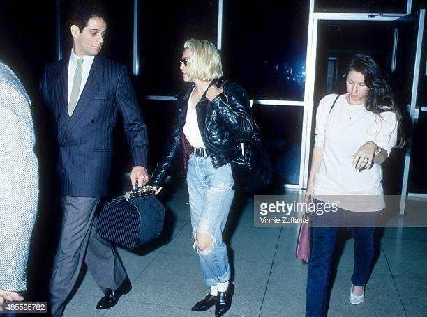Singer Madonna walks with her assistant Melissa Crowe at the JFK airport wearing waist high blue jeans and a leather jacket circa 1988 in New York...