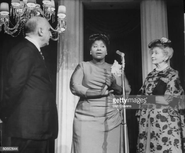 Singer Mahalia Jackson speaking at reception in hotel with composer Dimitri Tiomkin and Hedda Hopper