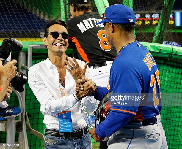 Singer Marc Anthony left speaks with bullpen coach Ricky Bones of the New York Mets during batting practice befiore the Miami Marlins played against...