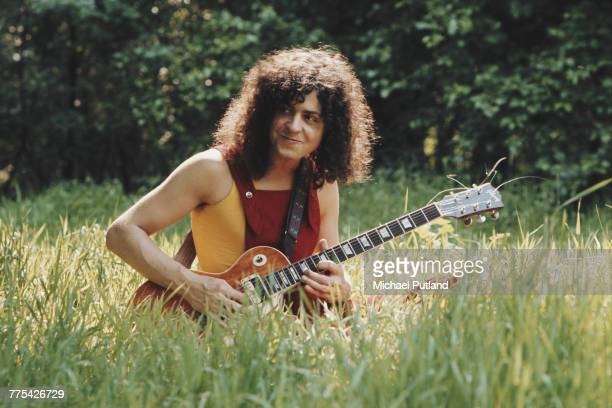 Singer Marc Bolan of English glam rock group TRex pictured sitting outdoors with his Gibson Les Paul guitar in a meadow in England in 1972