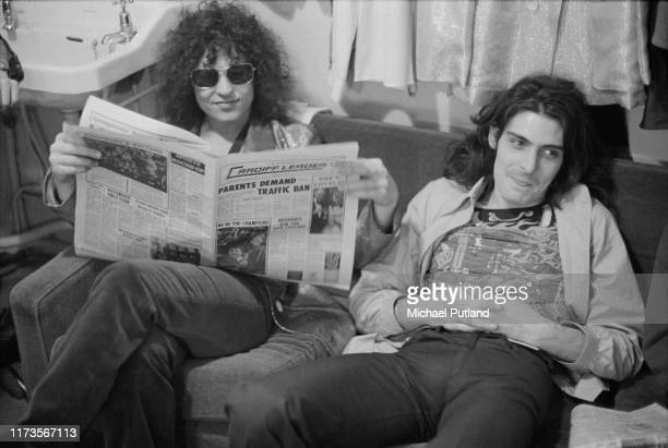 Singer Marc Bolan , on left, and percussionist Mickey Finn of English glam rock group T Rex, together on a sofa reading a copy of the local Cardiff...