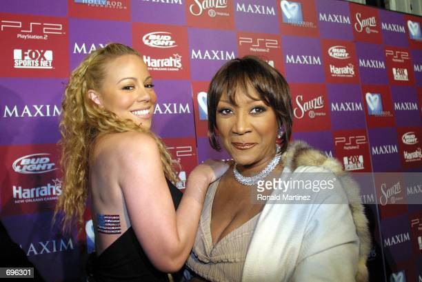 Singer Mariah Carey shows off an American flag with singer Patti LaBelle at Maxims Super Bowl benefit for the HollyRod Foundation February 1, 2002 in...