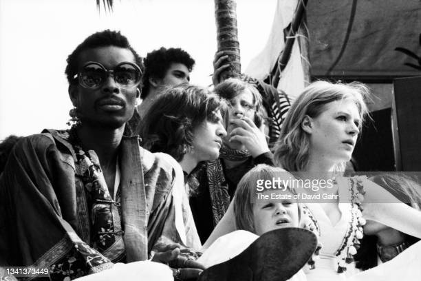 Singer Marianne Faithfull, with her young son, Nicholas Dunbar, and entourage, watches from the stage while rock group The Rolling Stones perform a...