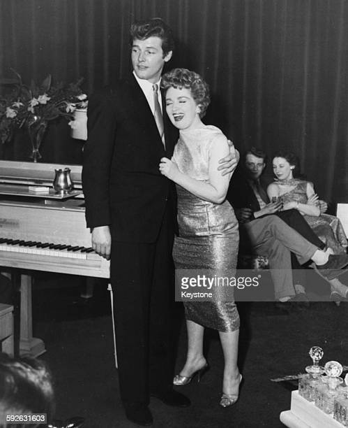 Singer Marion Ryan embracing actor Roger Moore as she performs her son 'Embraceable You' at a party to celebrate his new television show 'Ivanhoe' at...