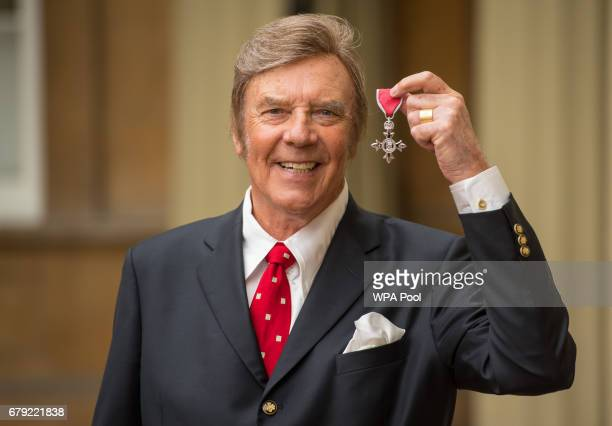 Singer Marty Wilde poses with his MBE medal from Queen Elizabeth II at an Investiture ceremony at Buckingham Palace on May 5 2017 in London England