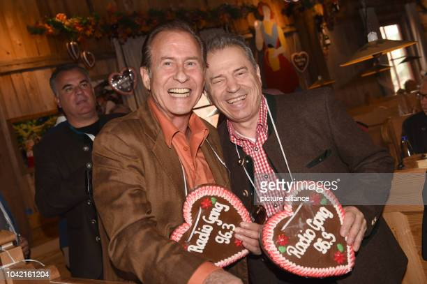 Singer Michael Holm and the singer of the band Spider Murphy Gang Gunther Siegl pose at the Kaeferzelt beer tent at the Oktoberfest in MunichGermany...