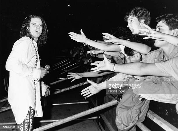 Singer Michael Hutchence, with the band INXS, watching crowds reach out to touch him as he performs at Wembley Stadium, London, June 30th 1988.