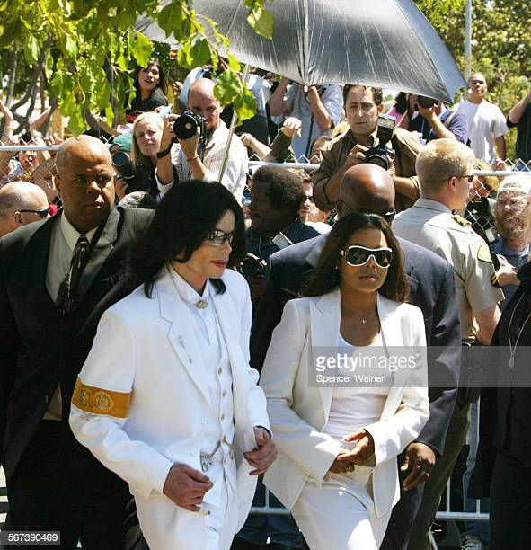 Singer Michael Jackson and sister Janet Jackson walk back to courthouse after greeting fans during a lunch break at a pretrial hearing in Santa Maria...