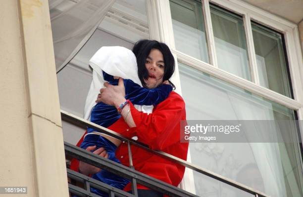 Singer Michael Jackson appears at the balcony of the Adlon Hotel with an unidentified child November 19 2002 in Berlin Germany Jackson is in Berlin...