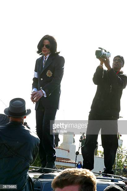 Singer Michael Jackson greets fans from the top of his car following his arraignment on child molestation charges on January 16 2004 in Santa Maria...
