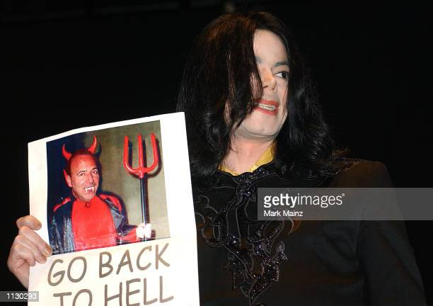"""Singer Michael Jackson holds a picture of Sony chairman, Tommy Mottola, during the """"30 Years of Magic"""" fan celebration by the Michael Jackson Fan..."""