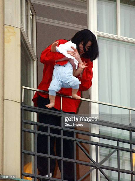 Singer Michael Jackson holds his eightmonthold son Prince Michael II over the balcony of the Adlon Hotel November 19 2002 in Berlin Germany Jackson...