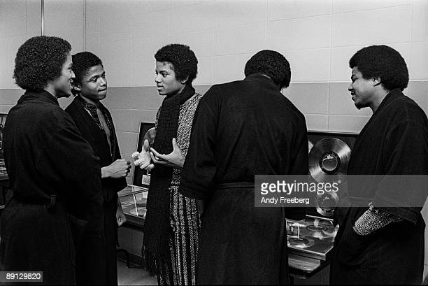 Singer Michael Jackson in center wearing long scarf backstage at Nassau Coliseum with the Jackson 5 New York 1980